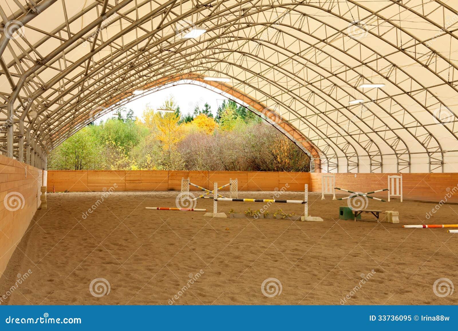 Покрытая открытая арена лошади с песком.