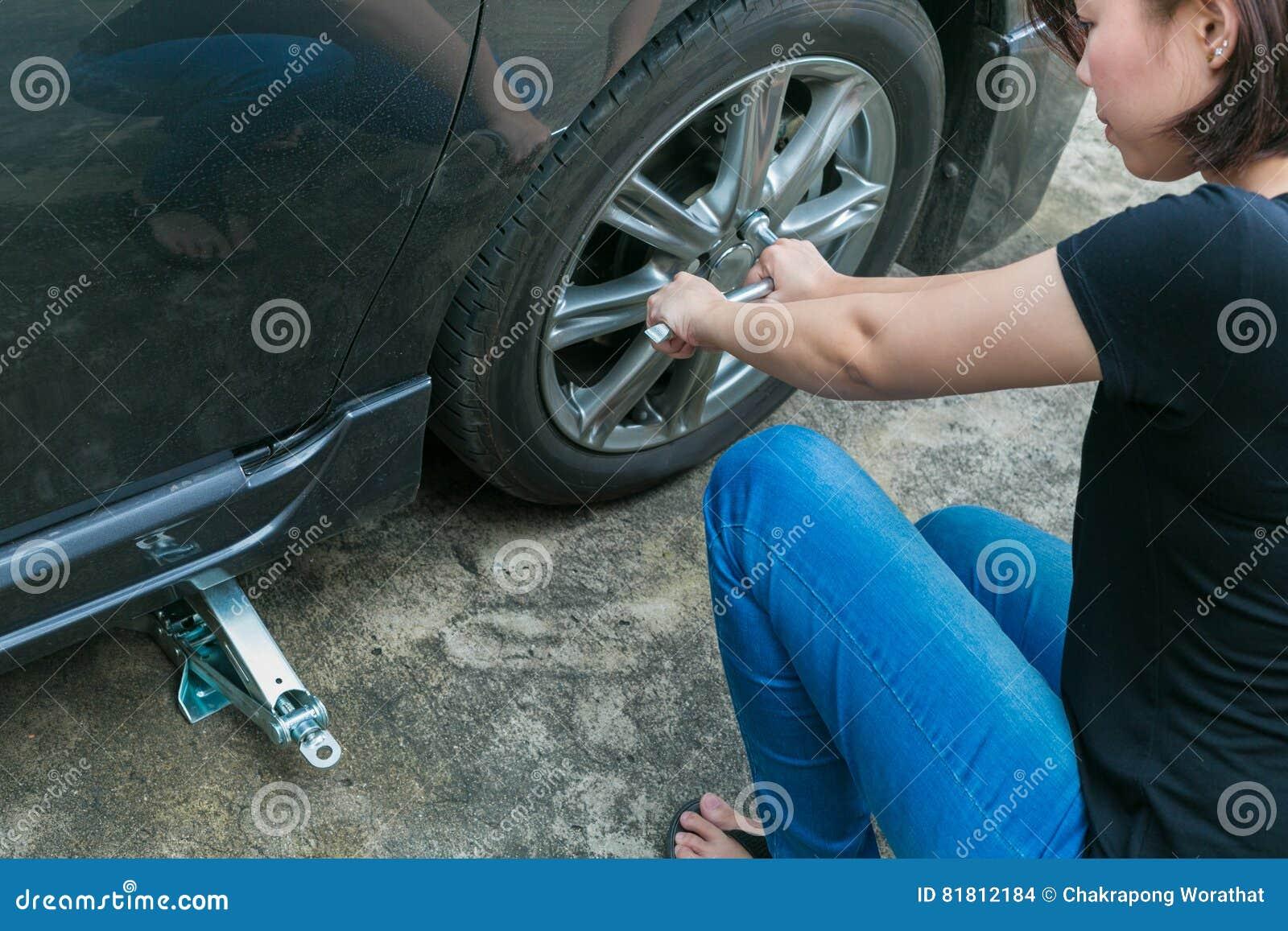Покрышка женского водителя изменяя на ее сломленном автомобиле