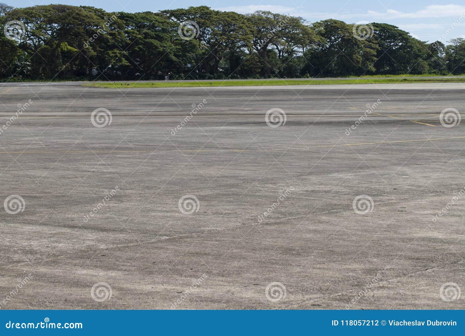 Поле авиапорта с растительностью Пустая взлётно-посадочная полоса в тропической стране Назначение перемещения летних каникулов