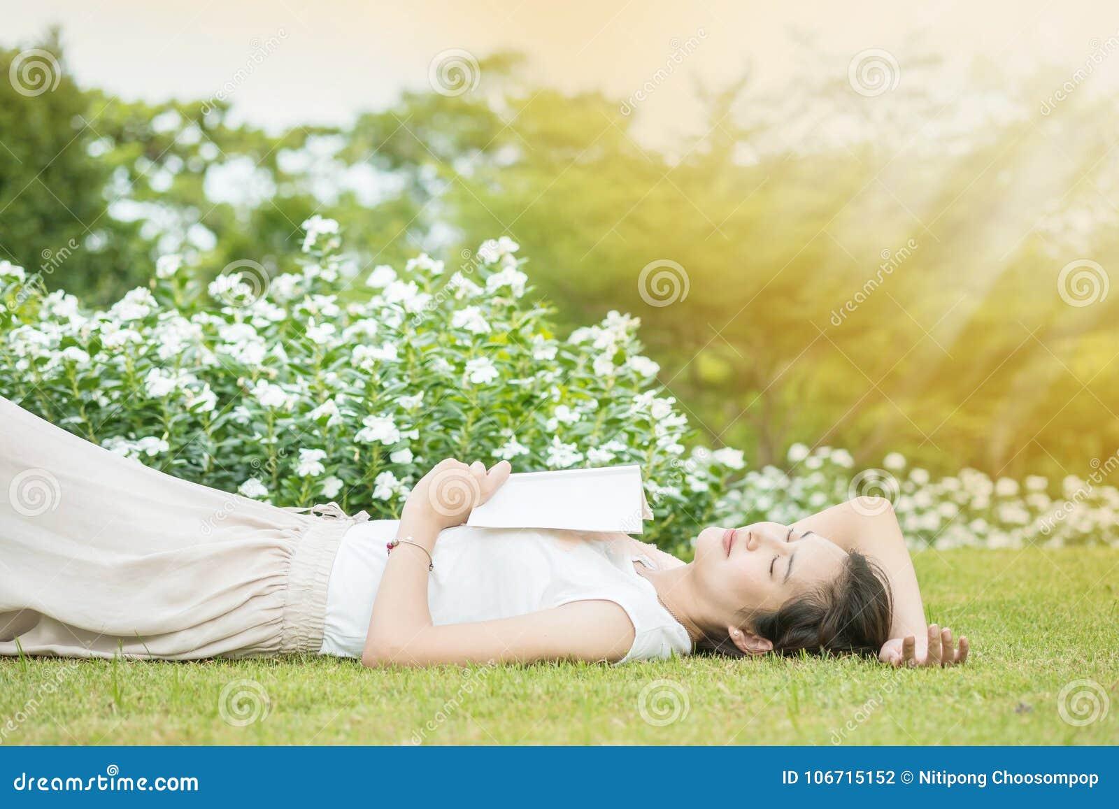 Поле травы азиатской женщины лежа после того как она утомляла для чтения книгу в после полудня