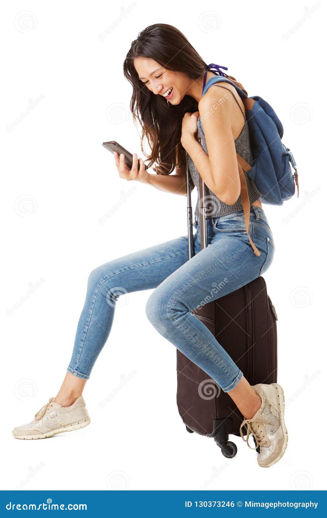 Полная сторона тела счастливого азиатского женского путешественника сидя на чемодане и смотря мобильный телефон против изолирован