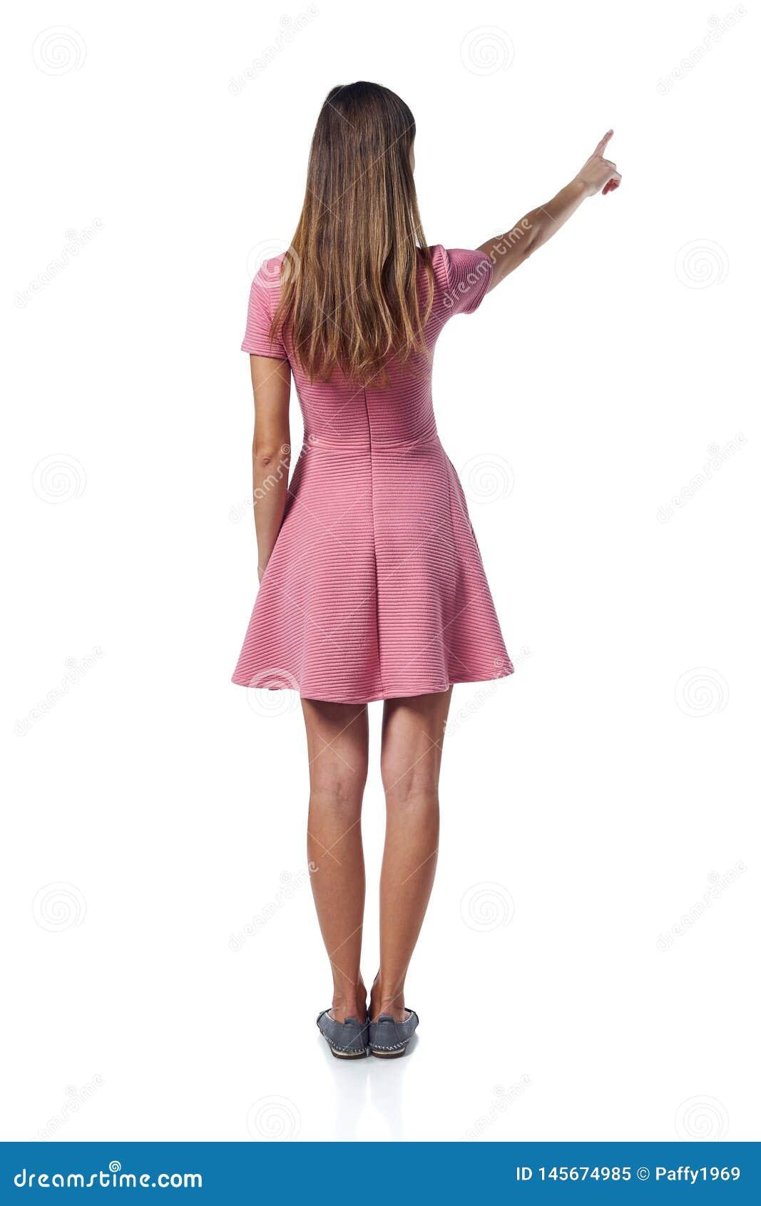 Полнометражная женщина в розовом платье указывая на сторону, задний взгляд