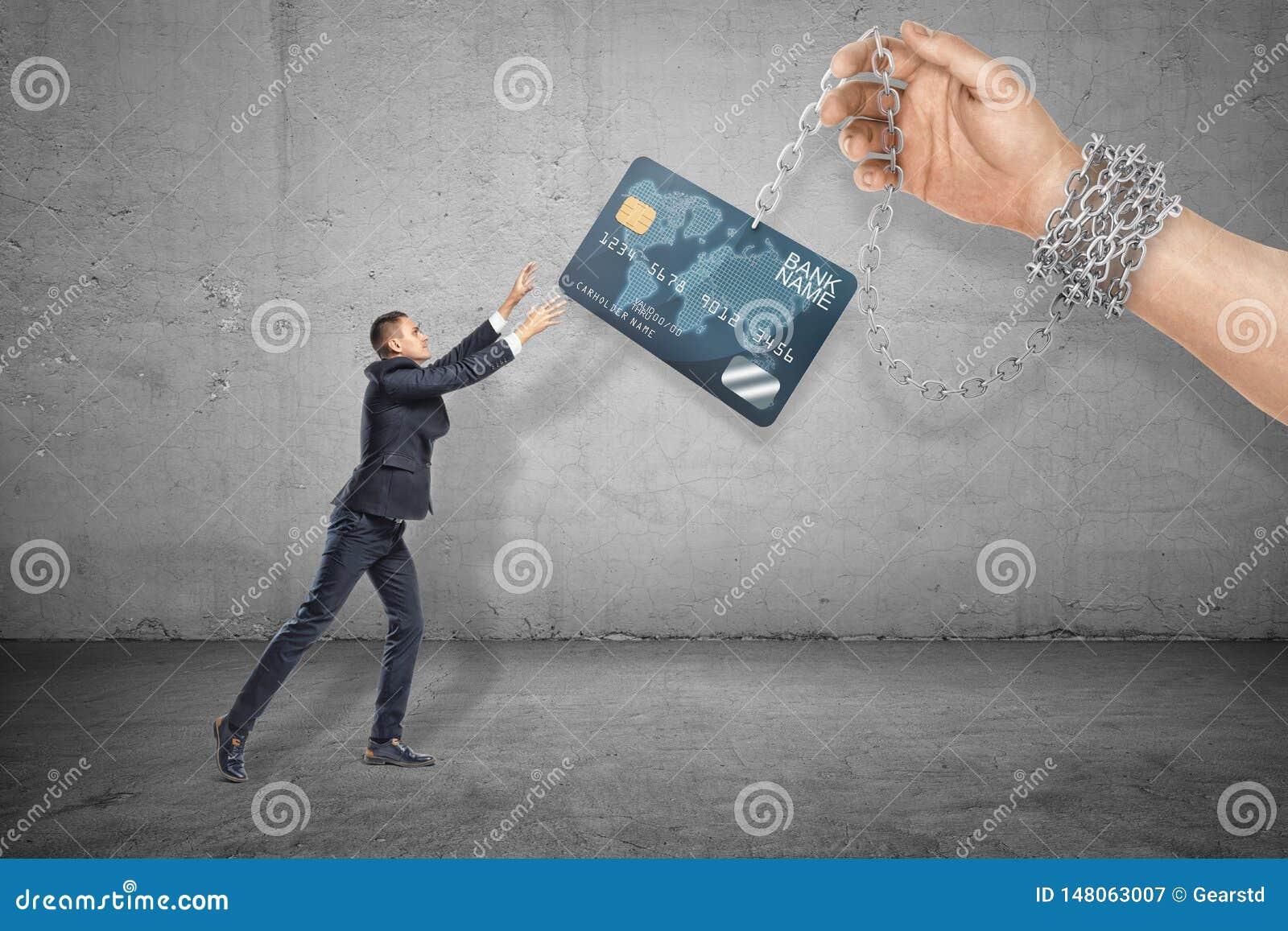 Полнометражный вид сбокуый меньшего бизнесмена достигая вне для того чтобы схватить кредитную карточку, который держит на цепи ог