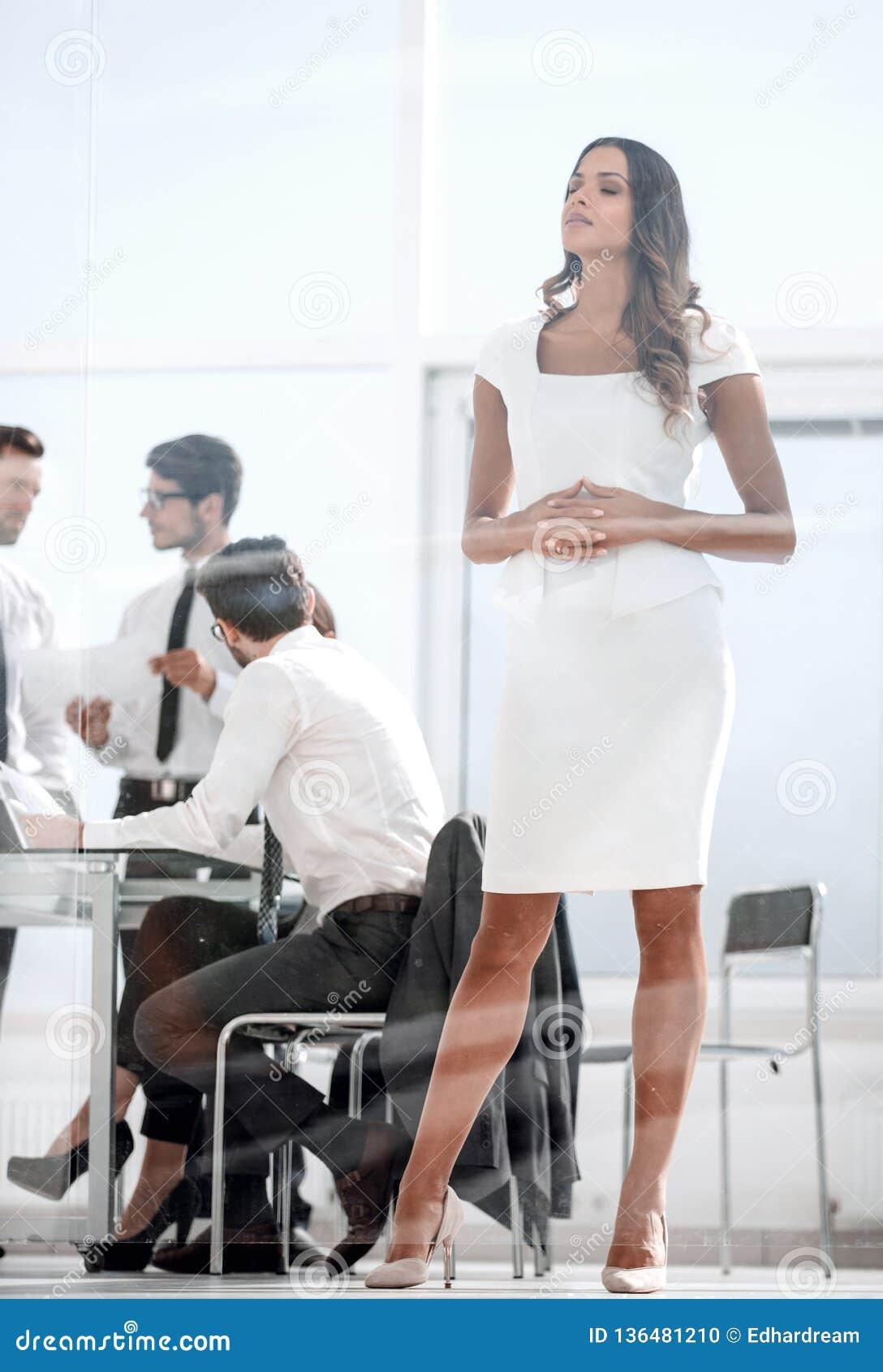 Полностью рост Молодая коммерсантка стоя в офисе