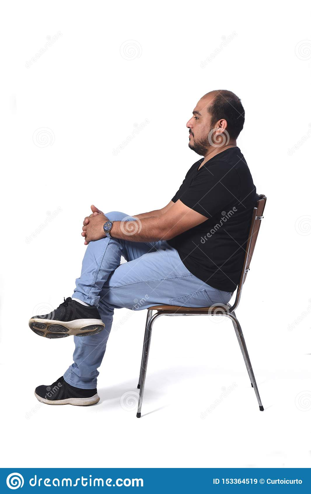 Полный портрет южного - американский человек сидя на стуле на белизне