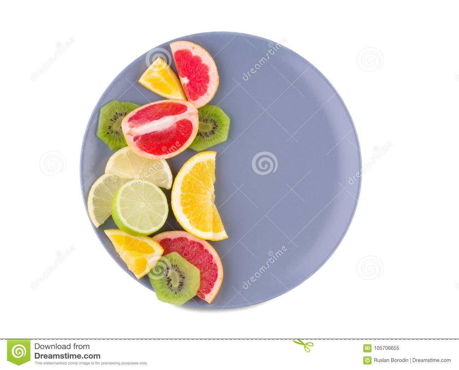 Половина плиты полна тропических плодоовощей на предпосылке изолированной белизной над взглядом