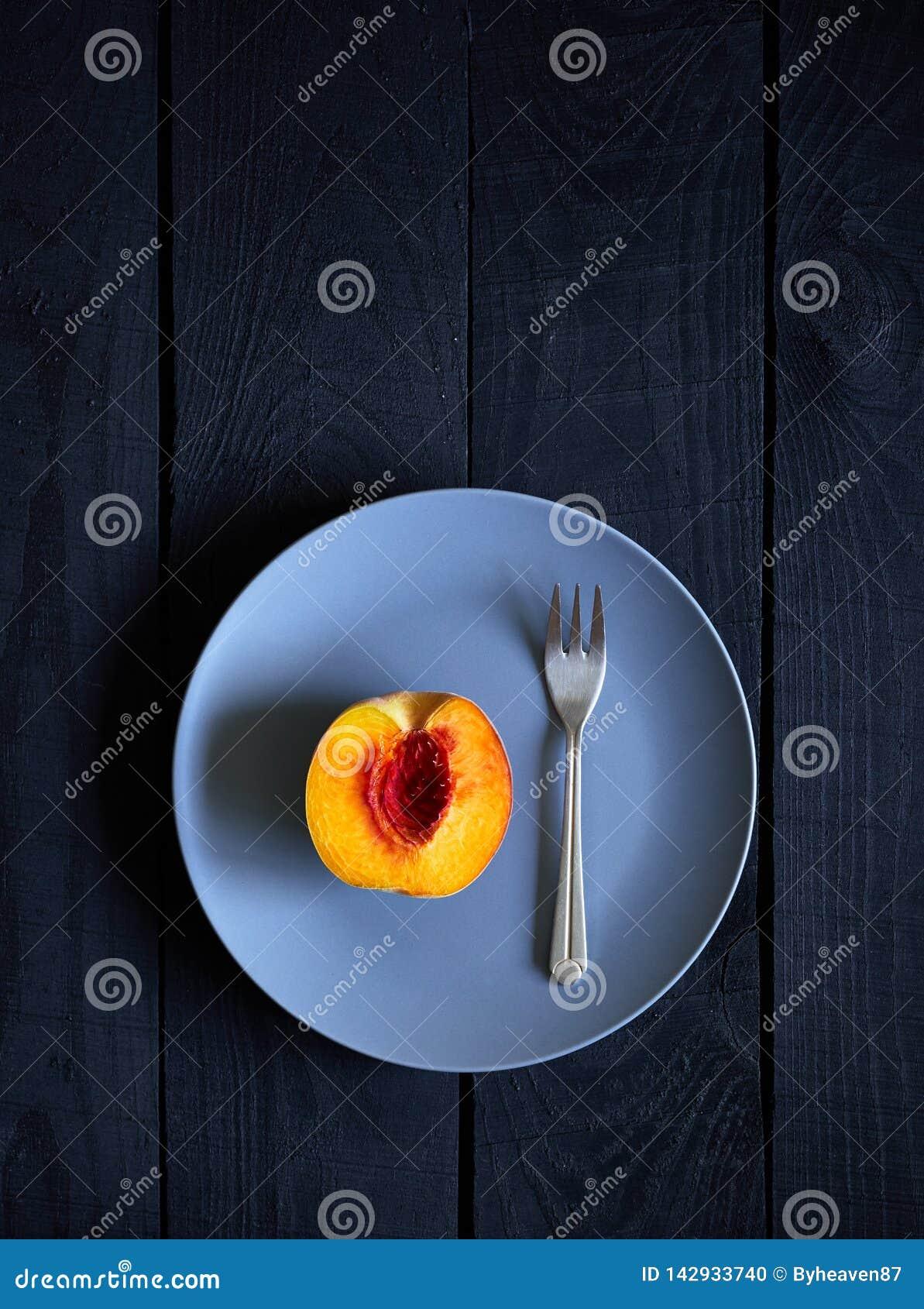 Половинные персик и вилка на плите