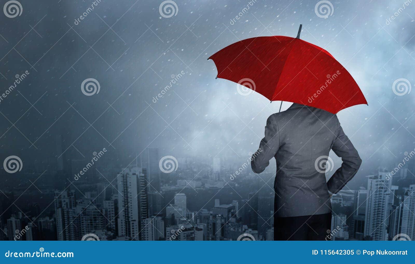 Положение бизнесмена пока держащ красный зонтик над штормом в огромной предпосылке дождя