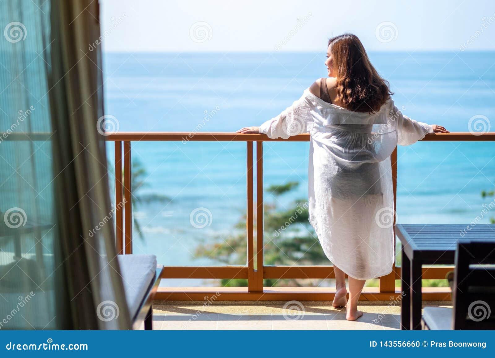 Положение женщины и насладиться наблюдать вид на море на балконе Стоковое  Фото - изображение насчитывающей пепельнообразные, одно: 143556660