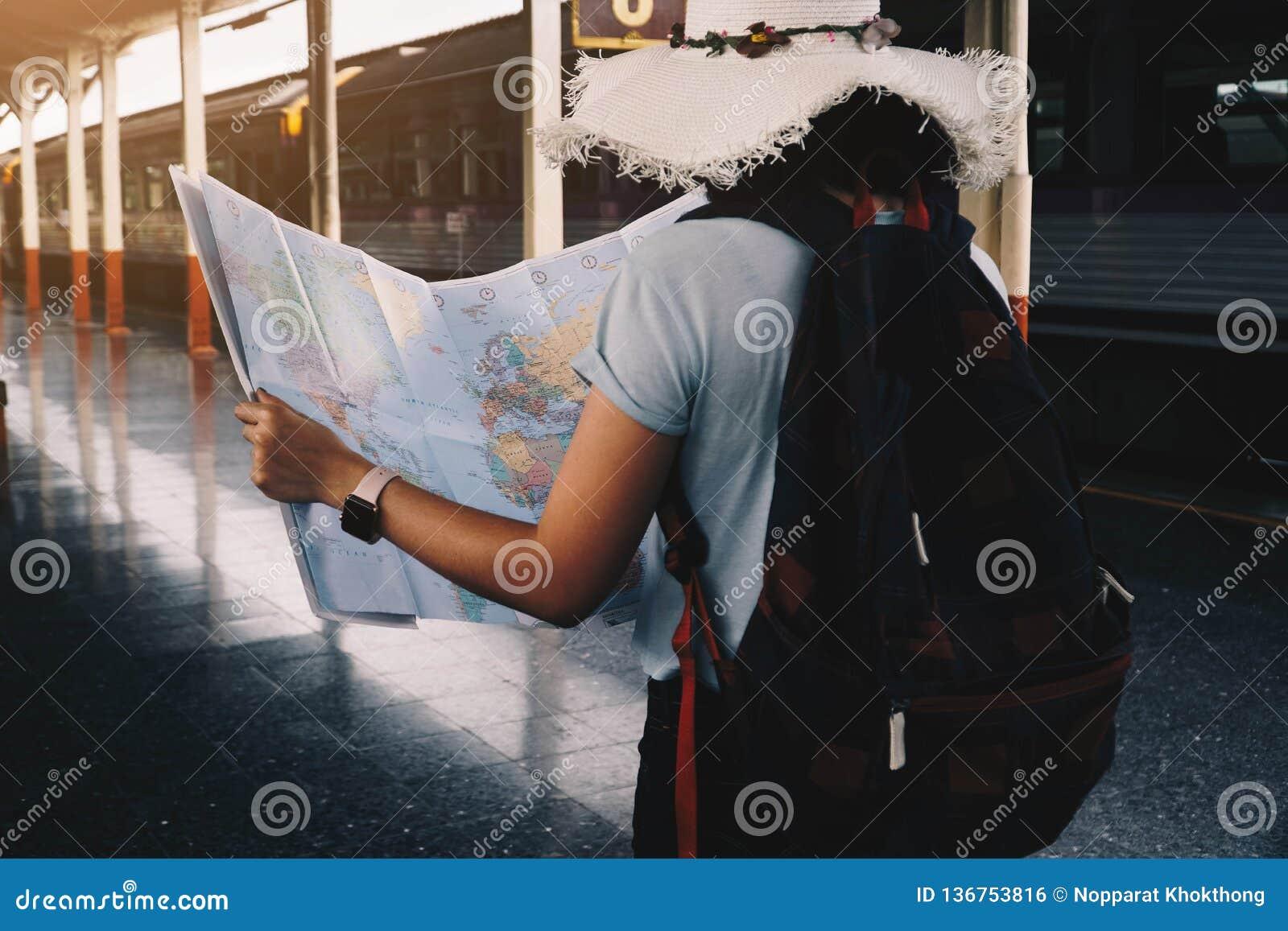 Положение карты удерживания путешественника молодой женщины на платформе на вокзале для перемещения Концепция перемещения поездом