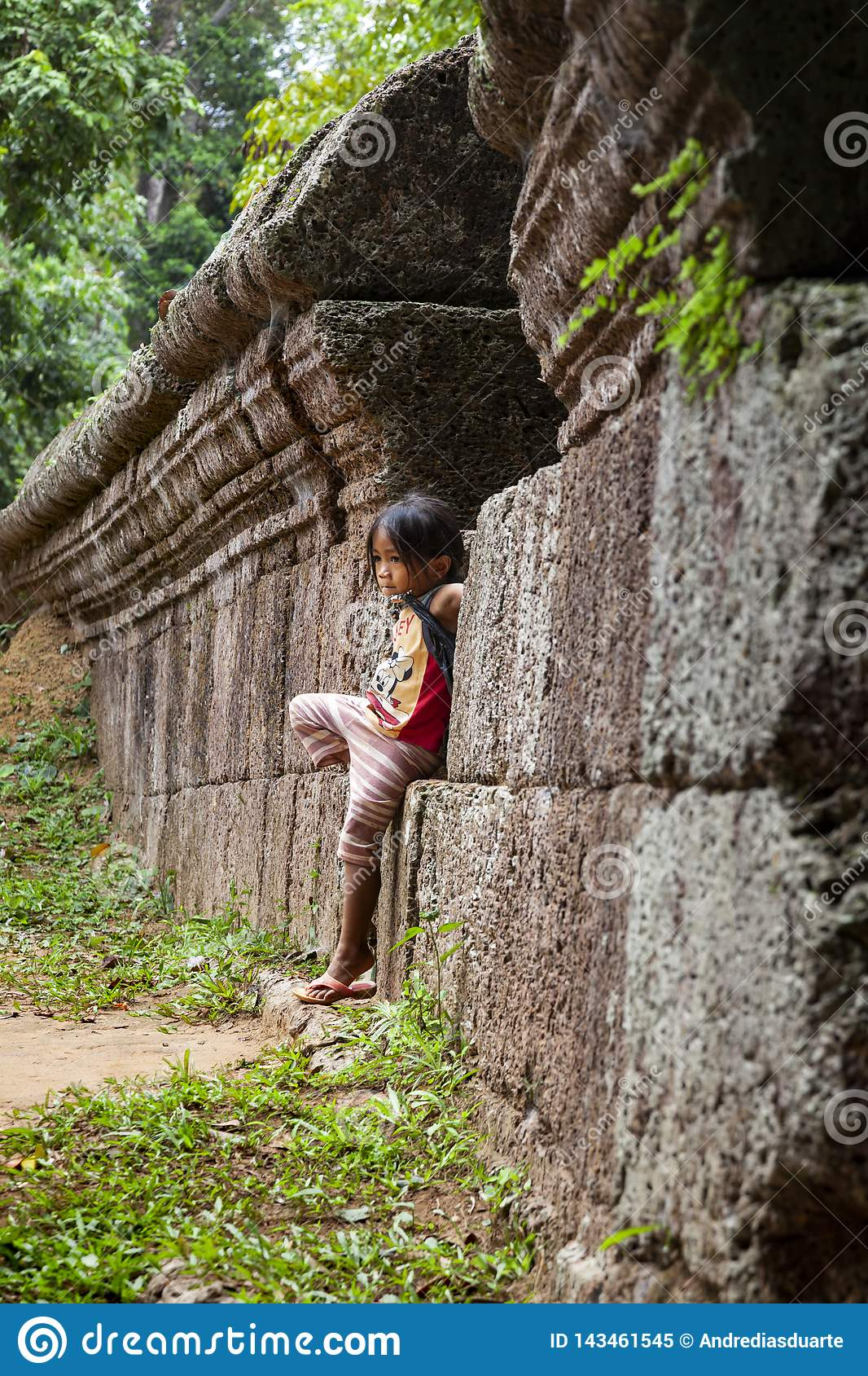 Положение маленькой девочки против старой каменной стены