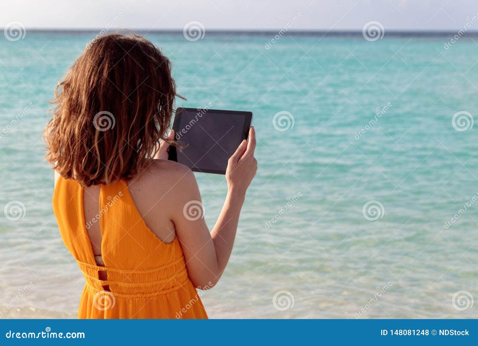Положение молодой женщины перед морем и использование ее планшета во время захода солнца