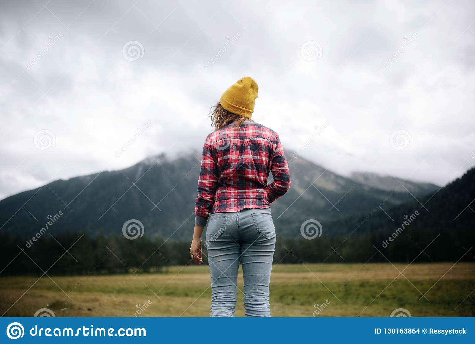 Положение путешественника женщин для того чтобы увидеть горы гористой местности