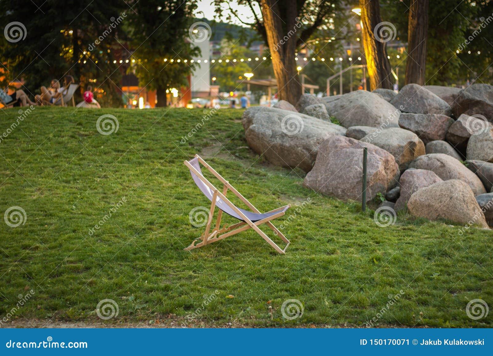 Положение шезлонга на зеленой траве на заходе солнца в Garnizon с утесами, деревьями и запачканными людьми на заднем плане