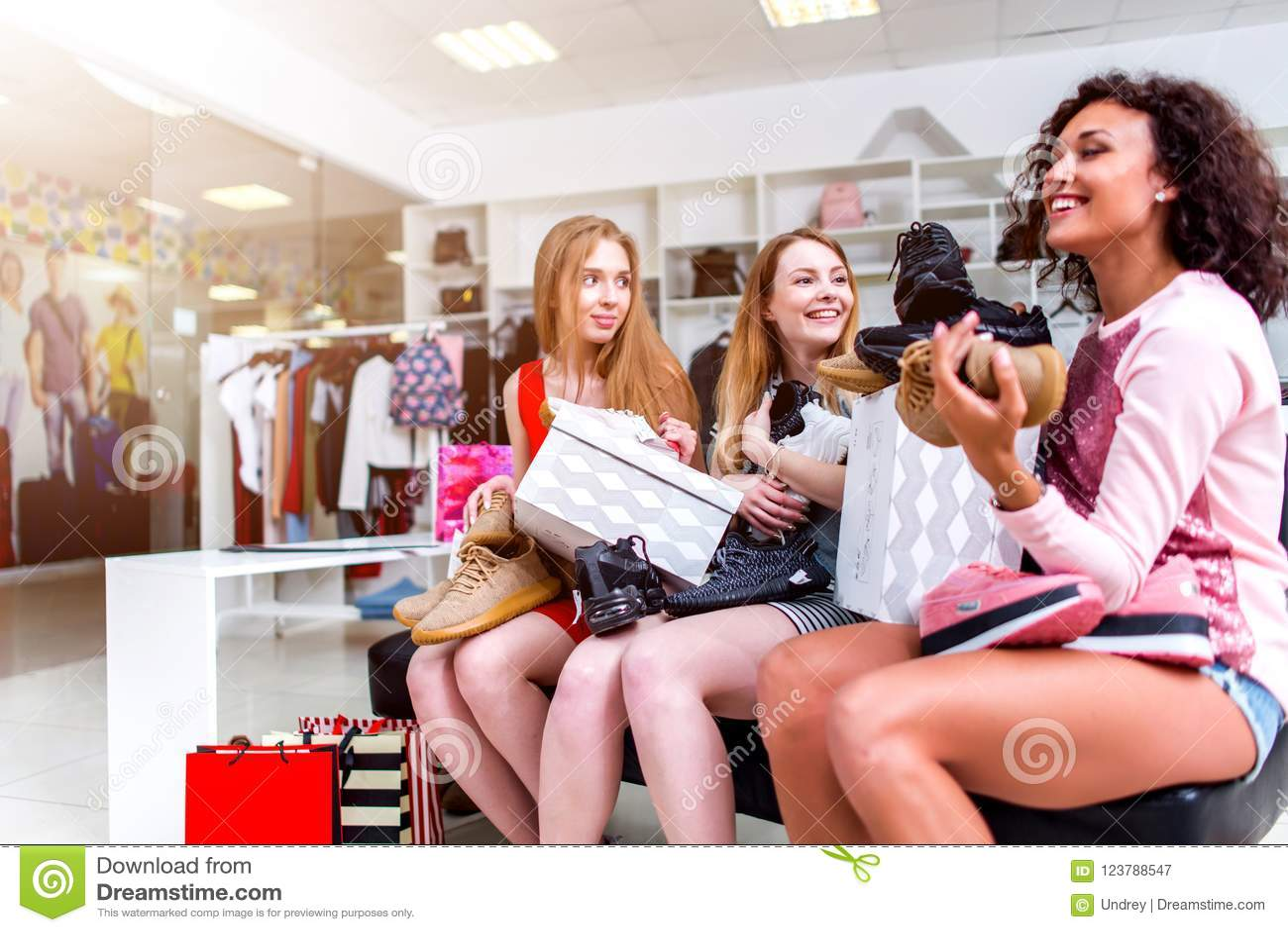 Положительные женские друзья счастливые с новым усаживанием с новыми ботинками и коробками на их подоле в магазине одежд