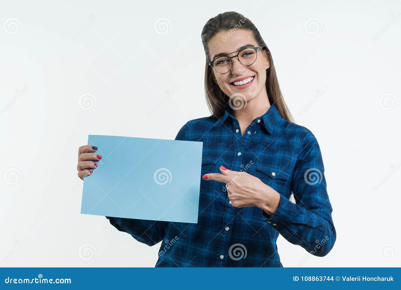 Положительный усмехаясь студент девушки держа очищенный лист голубой бумаги, указывая палец на бумагу