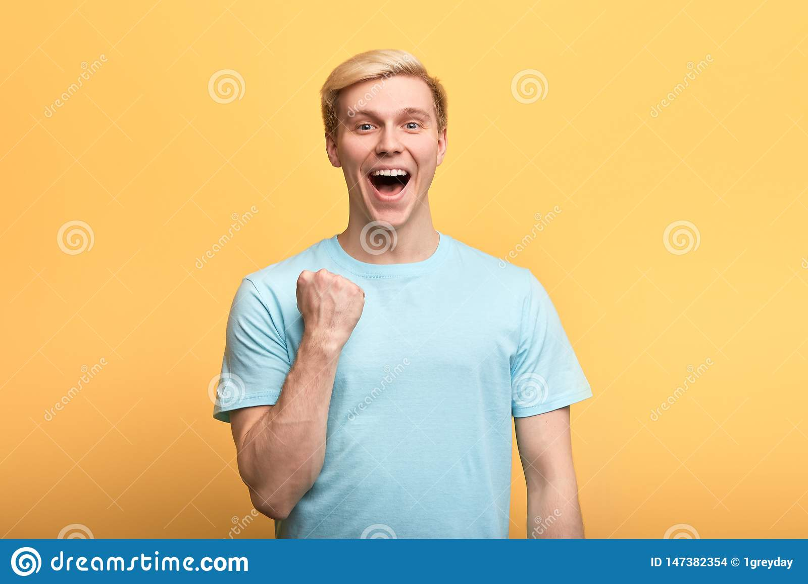 Положительный шикарный молодой эмоциональный человек поднимая сжатые кулаки в hooray жесте