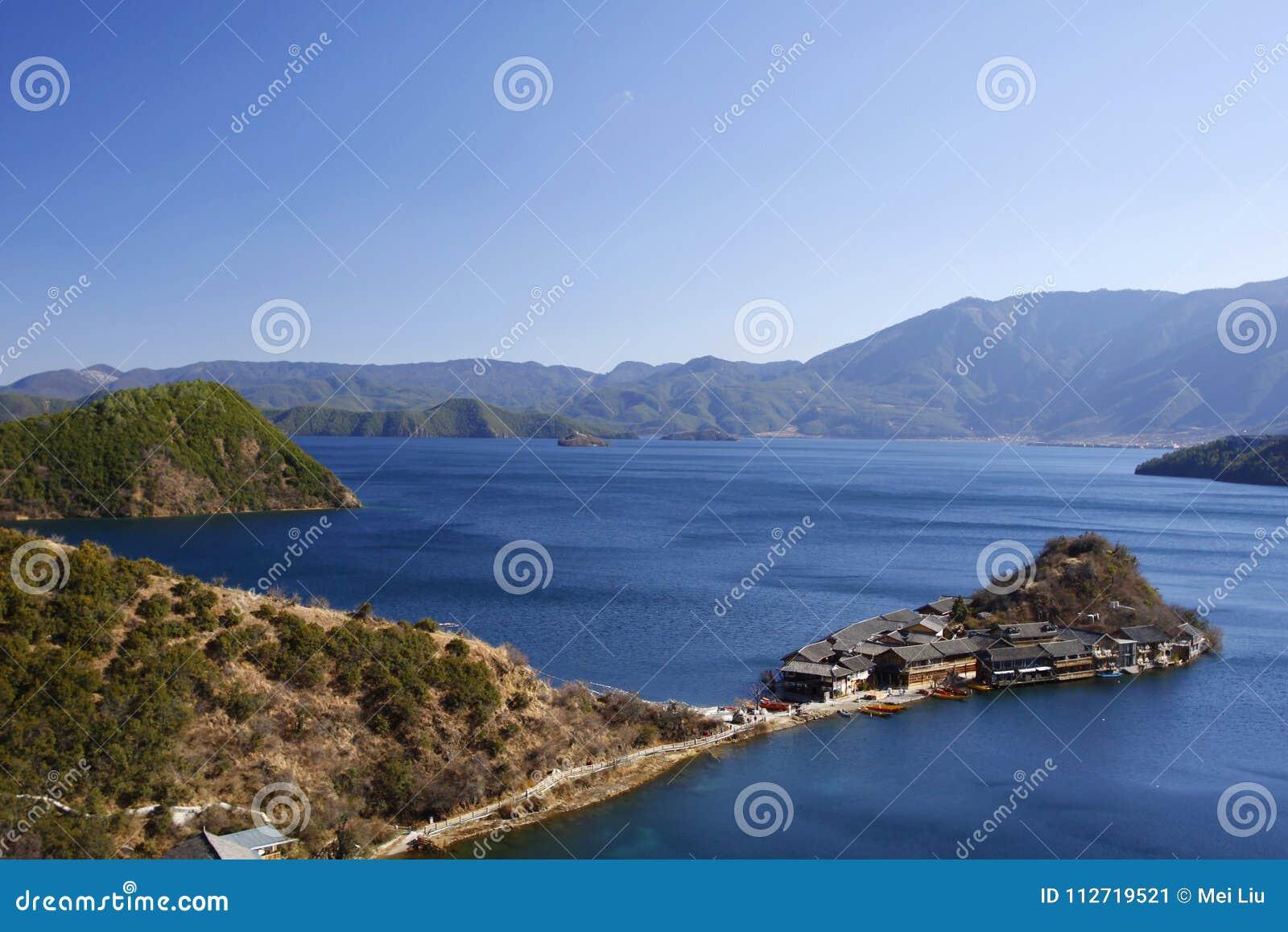 Полуостров Lige в открытом море озера Lugu и высоком небе