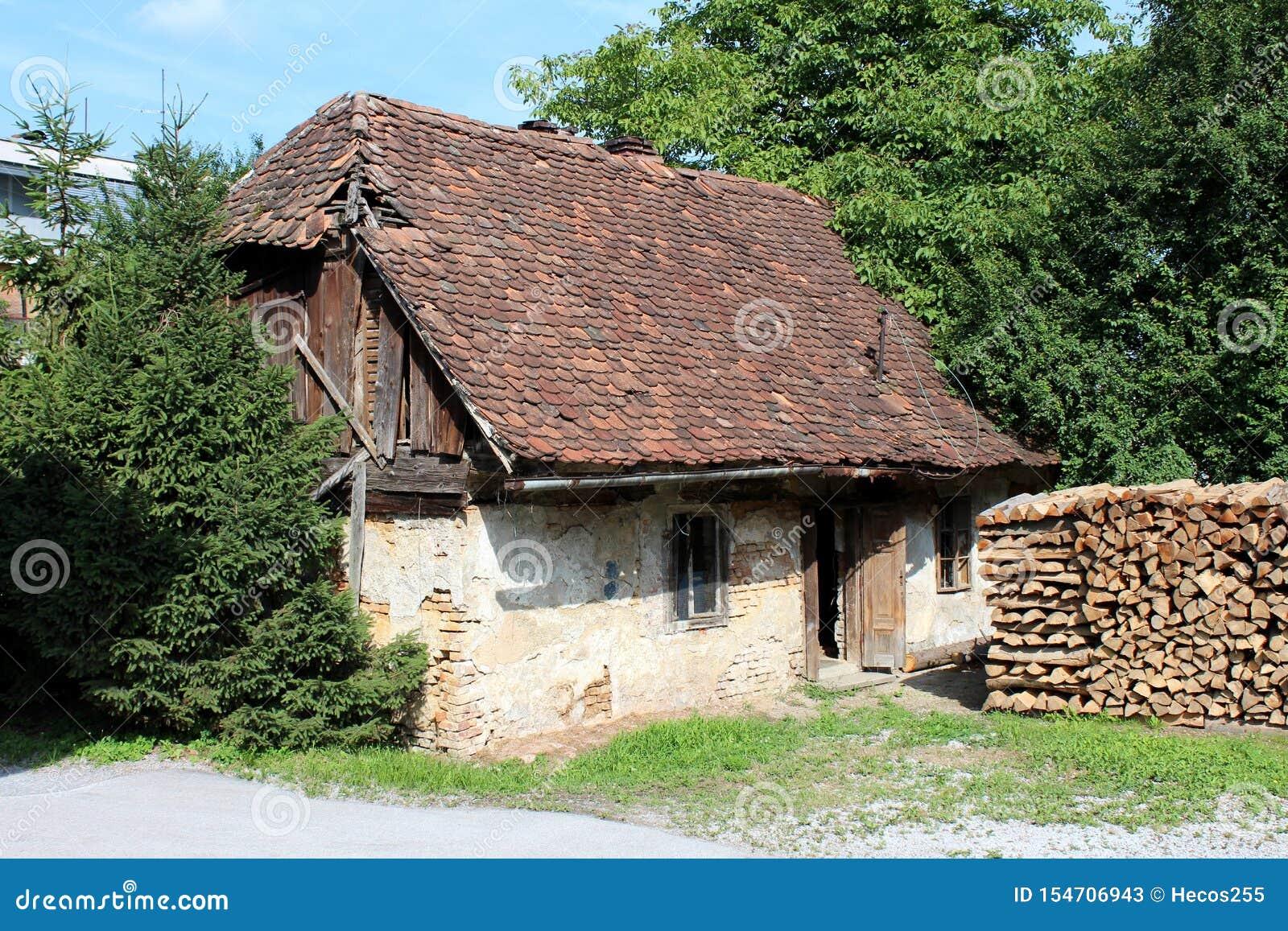 Получившийся отказ небольшой дом семьи с треснутыми стенами и разрушанным фасадом покрытыми с частично отсутствующими черепицами
