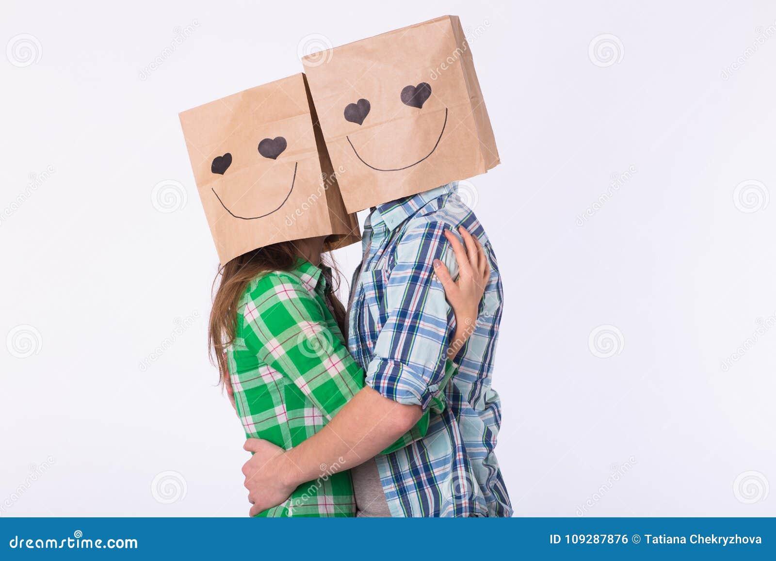 Полюбите пар покрывая их стороны с бумажной сумкой над белой предпосылкой