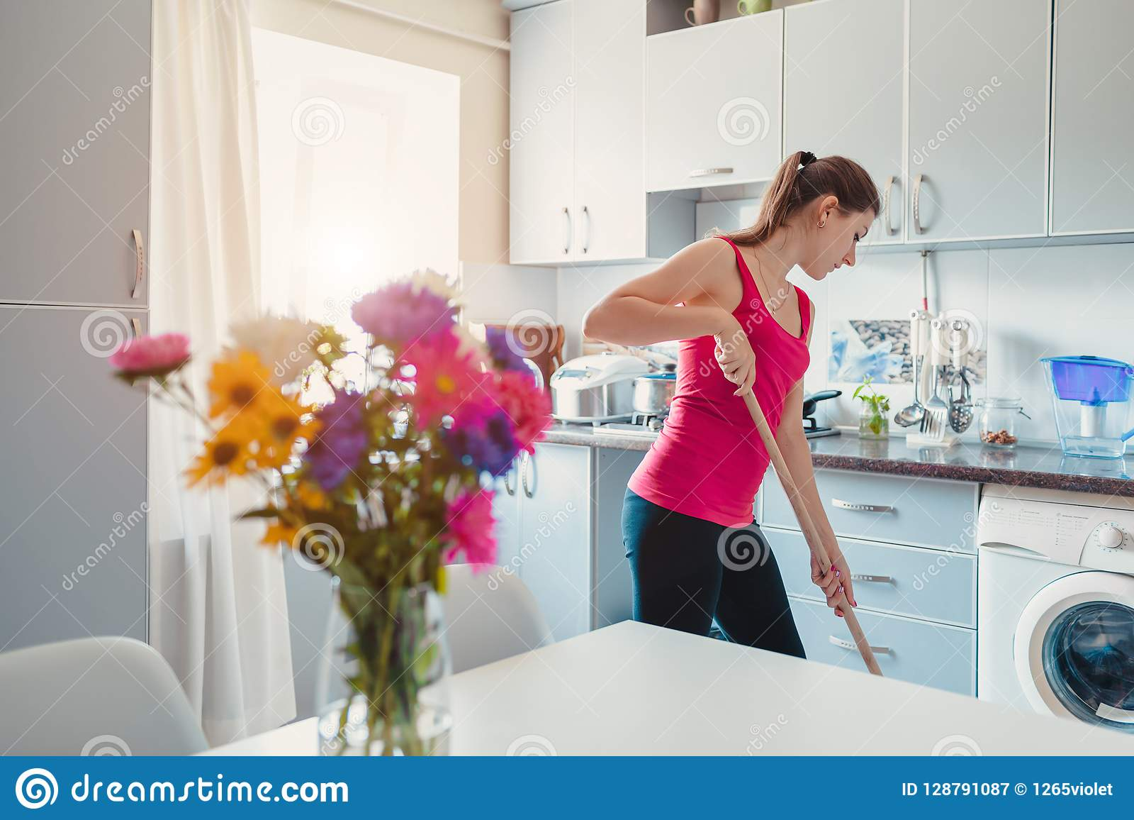 Пол молодой женщины моя с mop в современной кухне украшенной с цветками