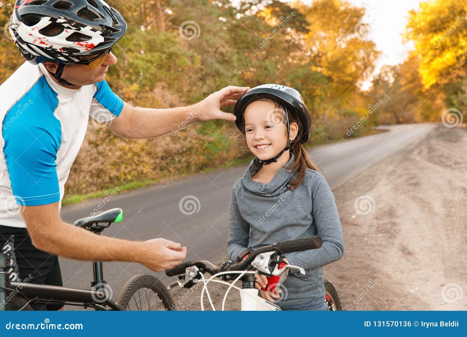 Помощь отца его езда сына велосипед