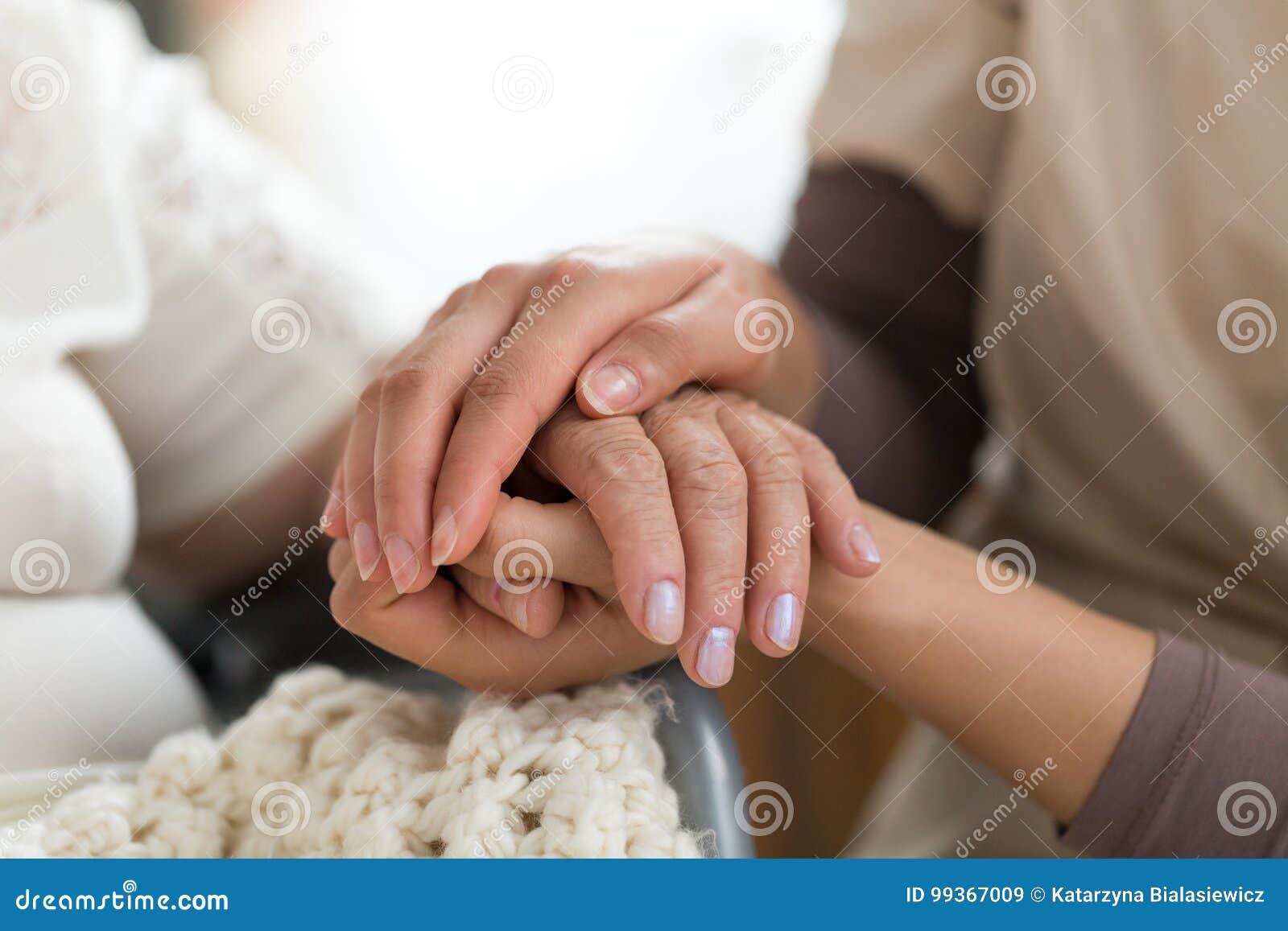 Попечитель держа старшие руки ` s женщины