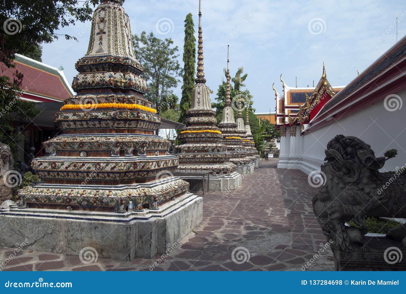 Попечитель на входе к монастырям около украшенного Phra Chedi Rai