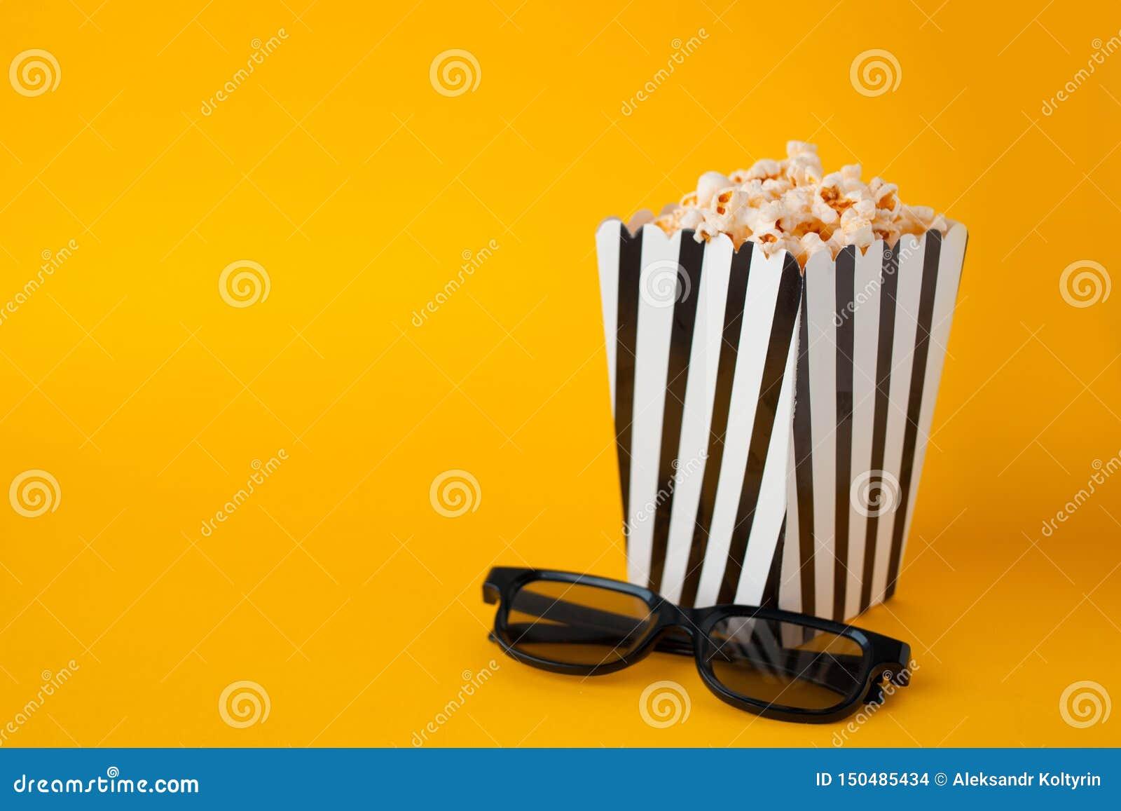 Попкорн в стойке бумажного мешка на желтых стеклах черноты 3d fnd взгляда сверху предпосылки