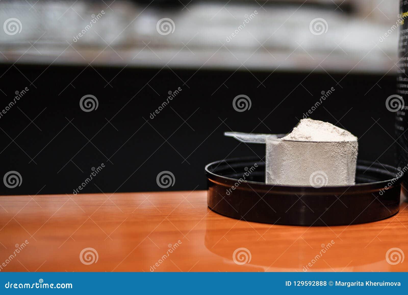 Порошок протеина Whey резвится дополнение культуризма Вид спереди белого ветроуловителя с ванильным порошком вкуса на деревянном