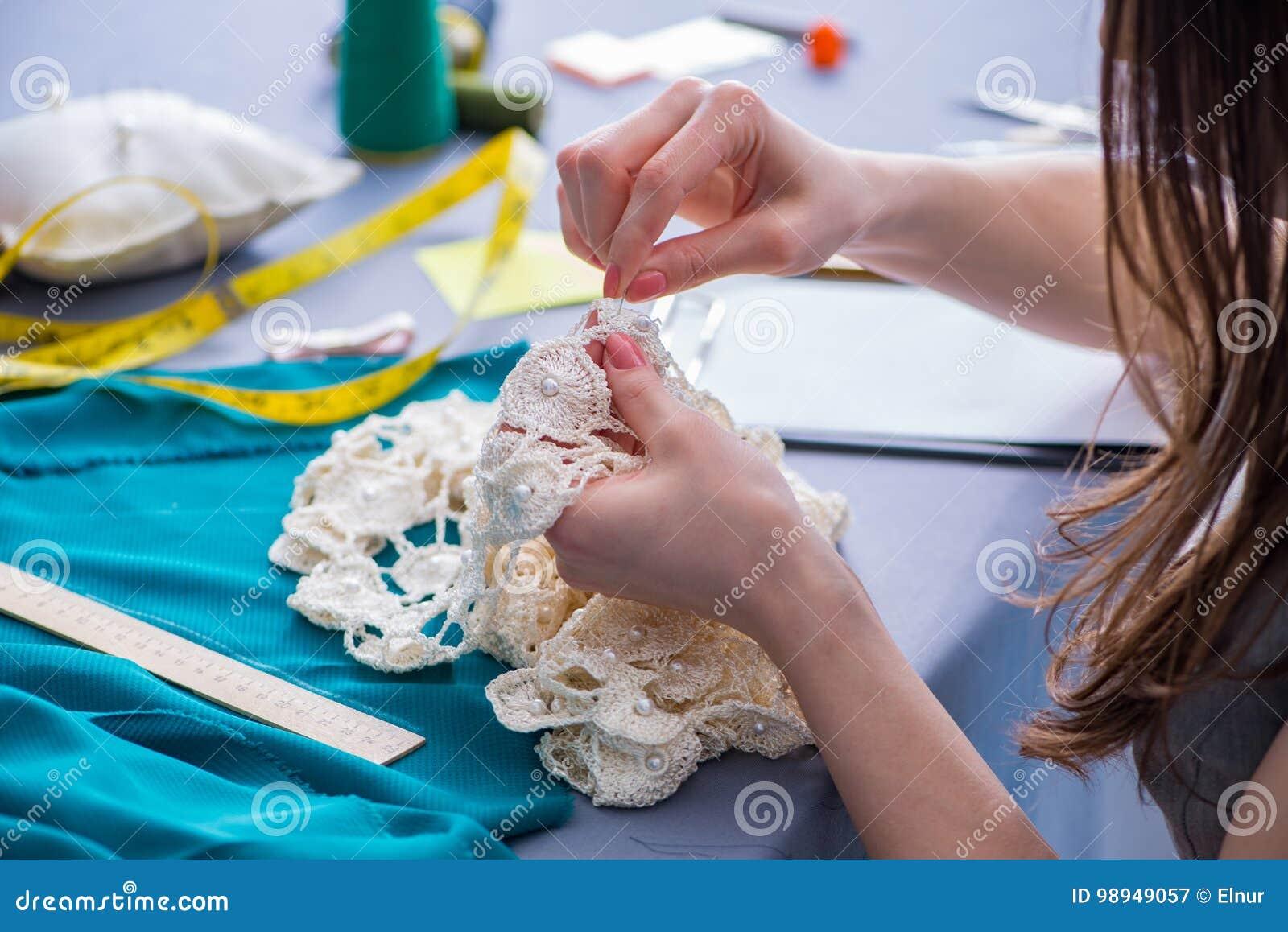 Портной женщины работая на одежде шить шить измеряя fa