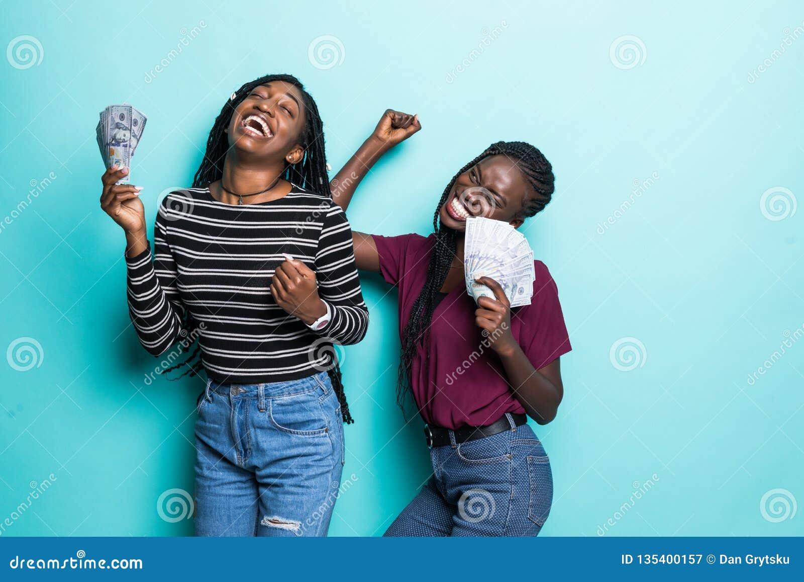 Портрет 2 африканских услаженных девушек радуясь выигрыш и танцуя пока держащ вентиляторы денег наличных денег изолированный над