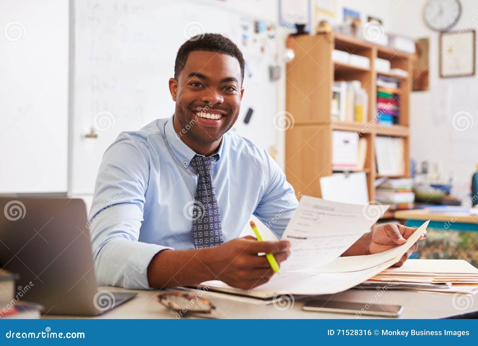 Портрет Афро-американского мужского учителя работая на столе