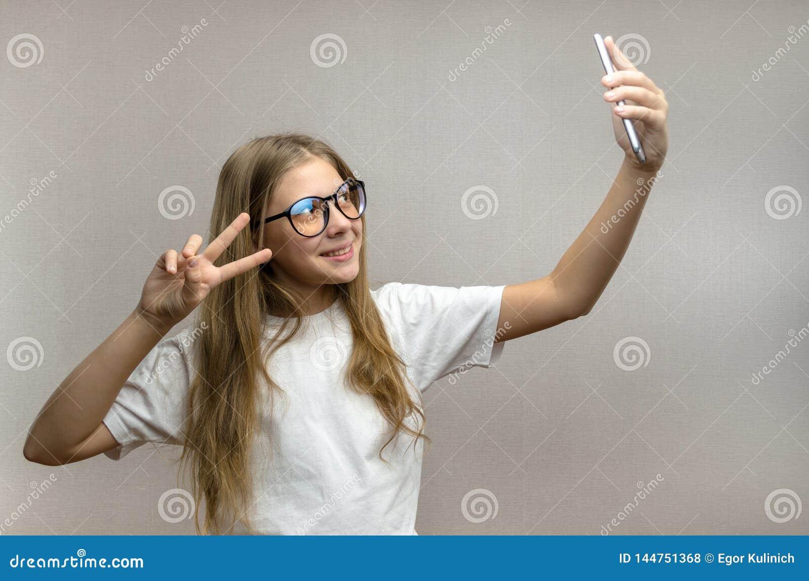 Портрет белокурой девушки которая принимает selfie на ее смартфоне Современные технологии Молодой блоггер