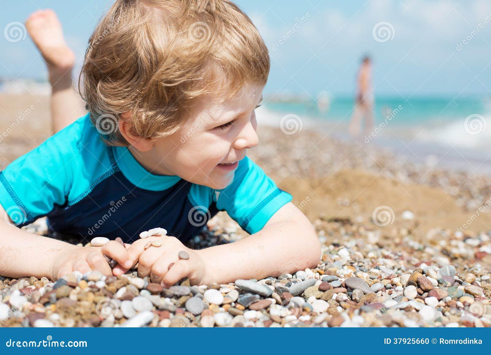 Портрет белокурого мальчика малыша на пляже в лете.