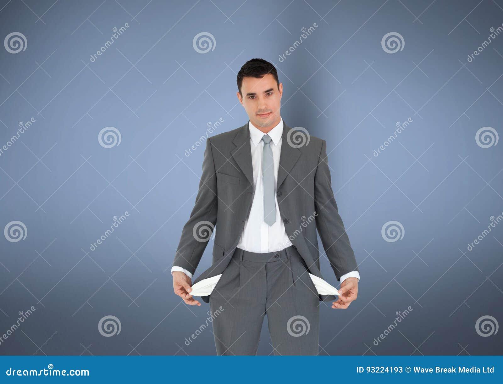 Портрет бизнесмена при пустые карманн стоя против серой предпосылки не представляя никакие деньги
