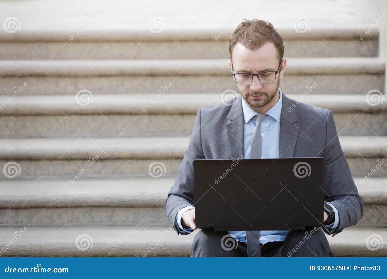 Портрет бизнесмена сидя на лестницах и работая на l