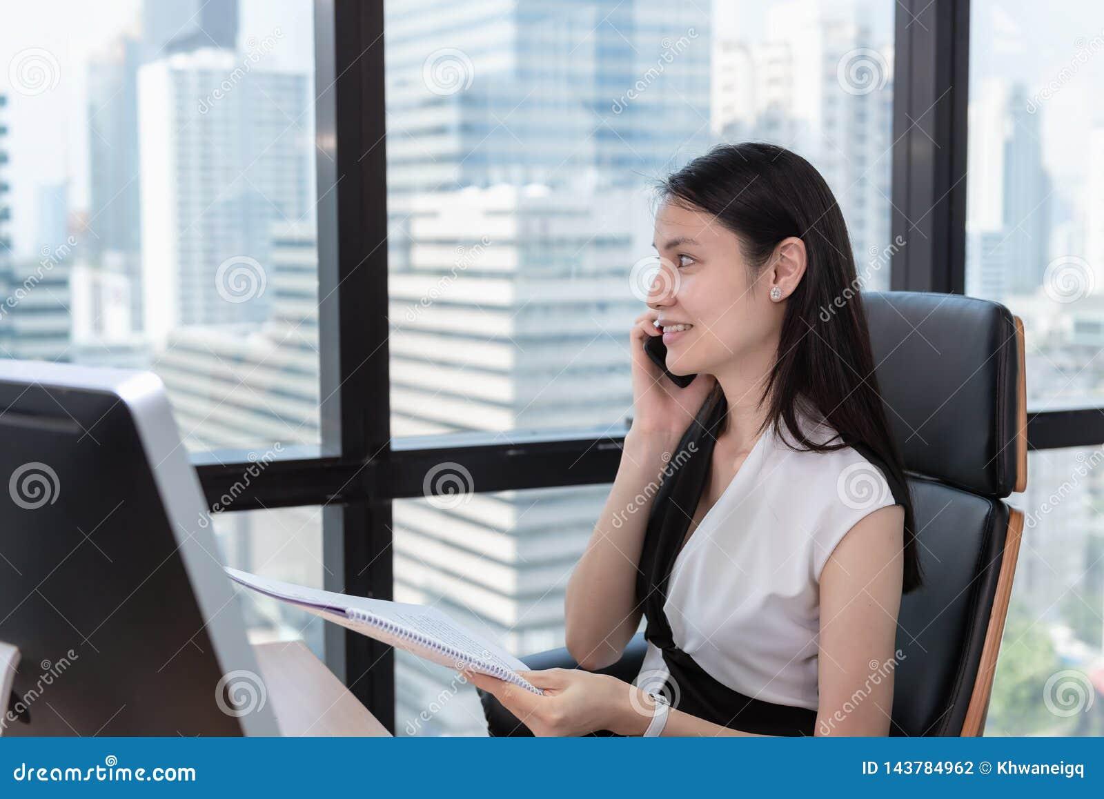 Портрет бизнес-леди говорит на мобильном телефоне в рабочем месте офиса, привлекательная красивая коммерсантка говорит дальше