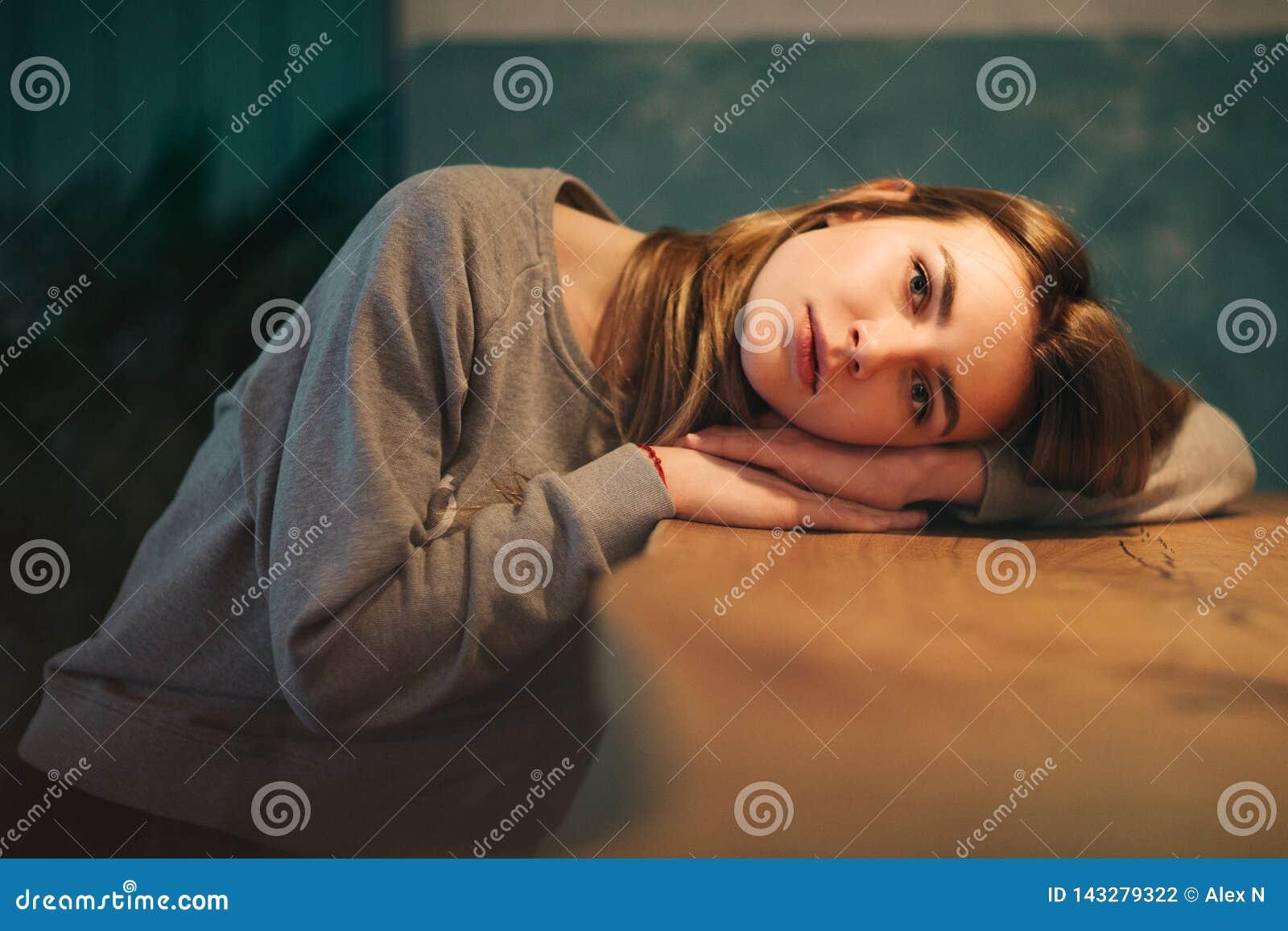 Портрет блондинкы с длинными волосами, головой лежит на таблице
