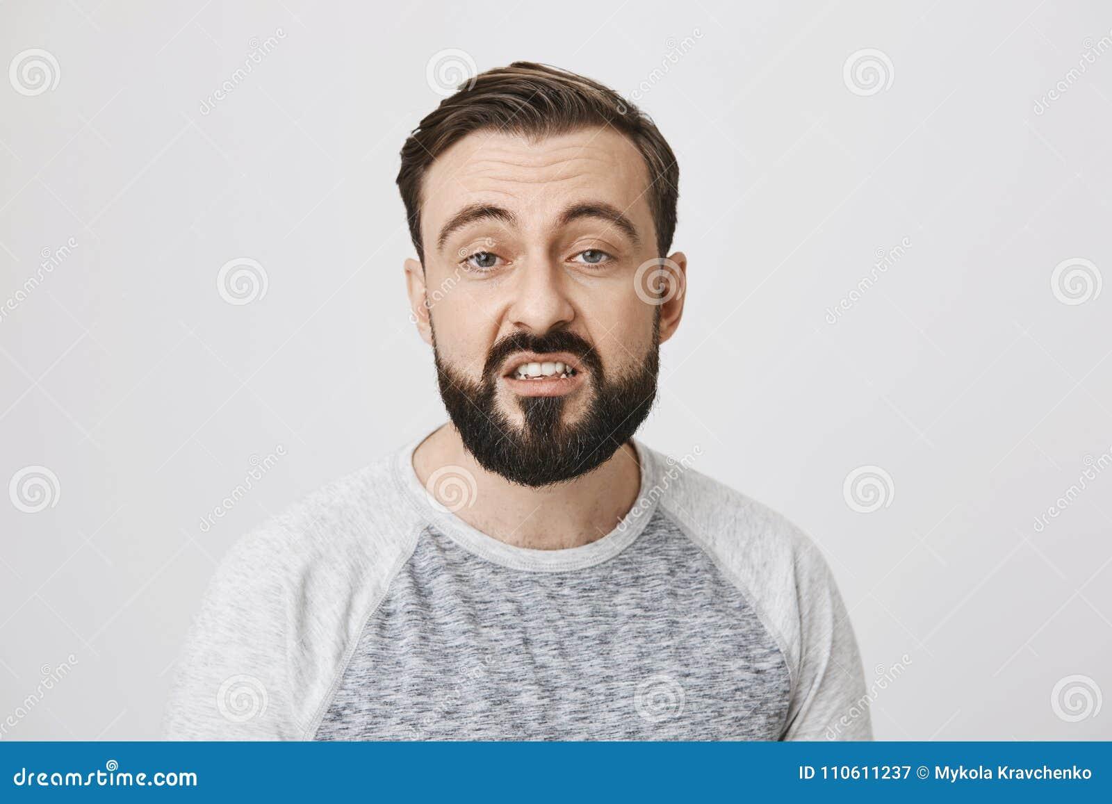 Портрет бородатого европейского человека выражая отвращение с раскрытым ртом и поданным вверх выражением, стоя над серым цветом