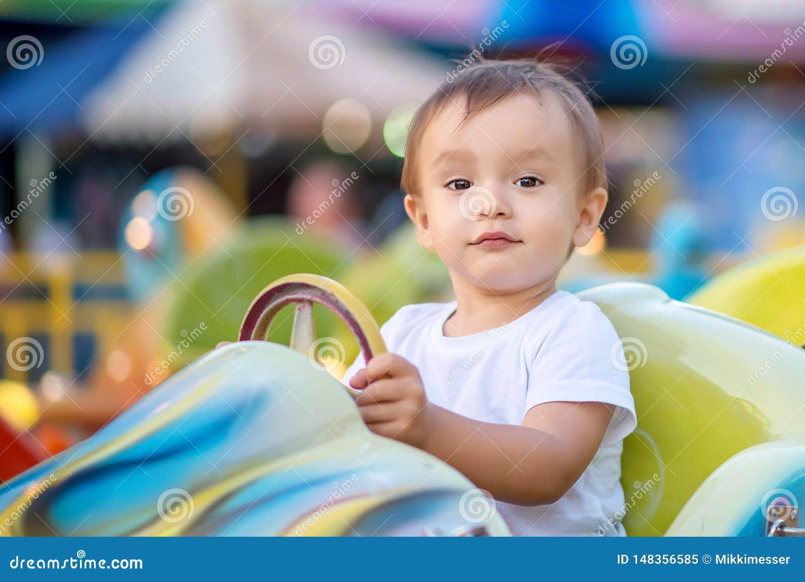 Портрет будущего участвуя в гонке чемпиона: ребенок малыша сидя на меньшем ярком автомобиле на весел-идти-круглом в тематическом
