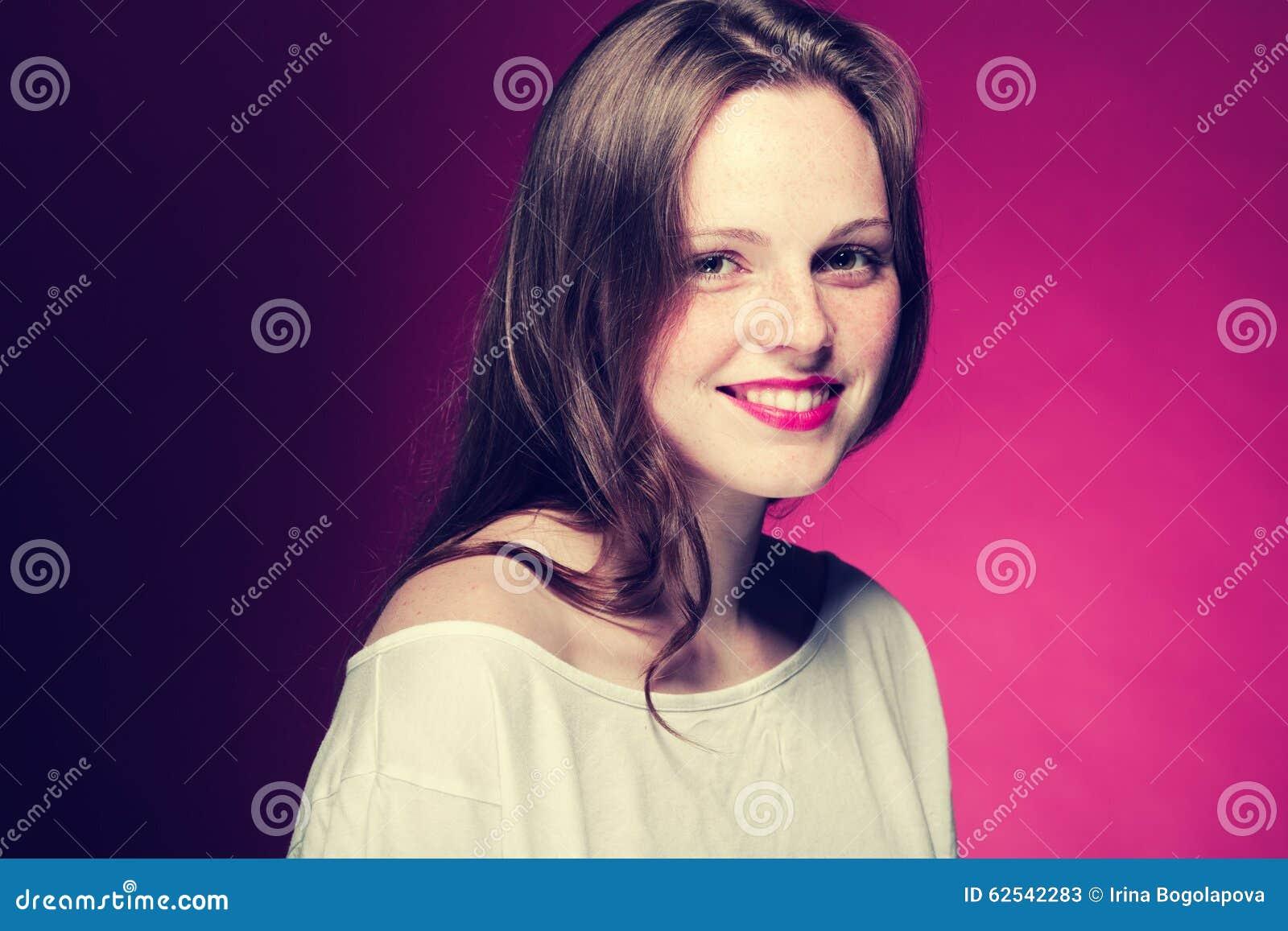 Портрет веснушки женщины на предпосылке цвета красной и розовой
