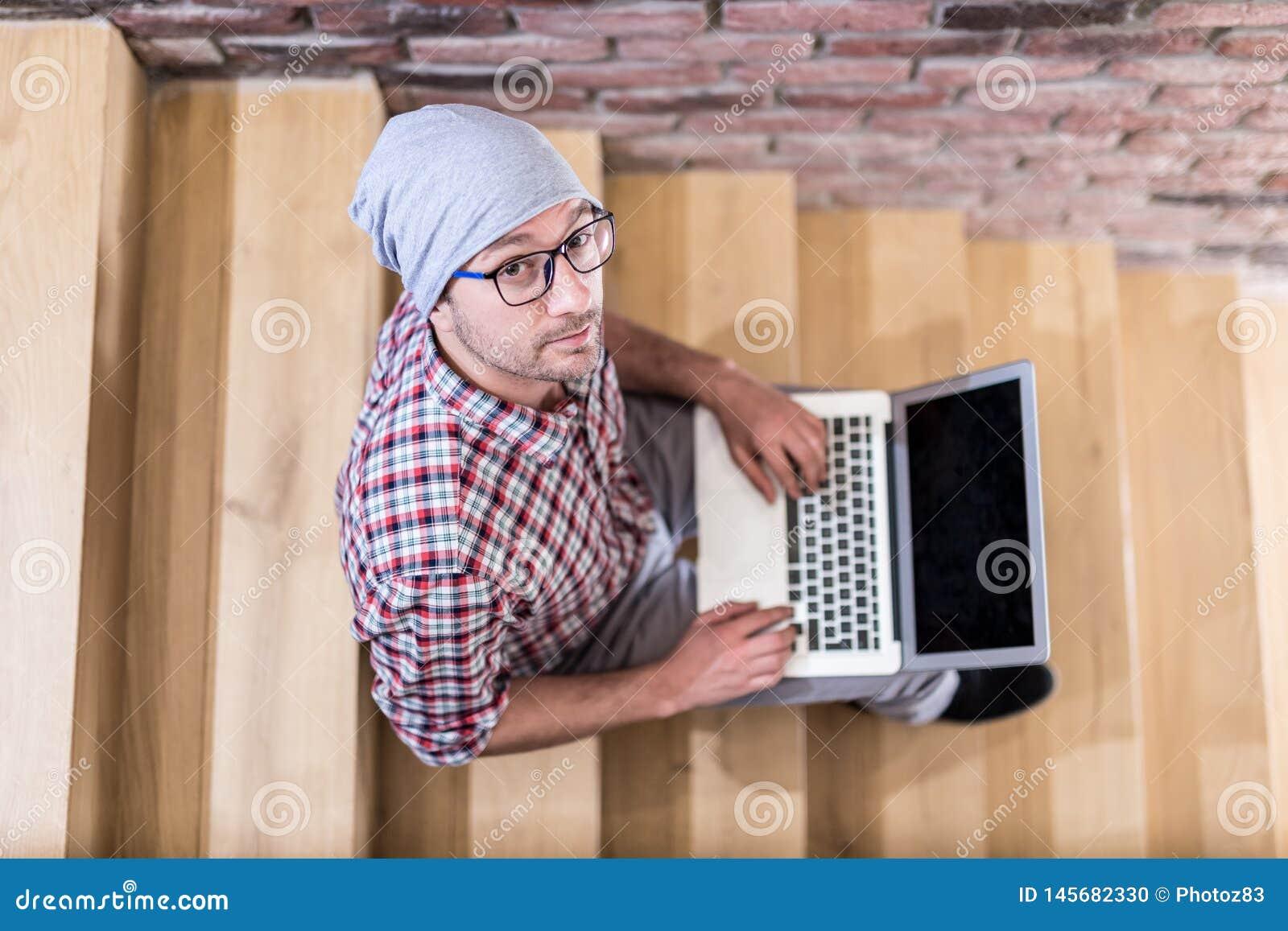 Портрет взгляда высокого угла модного блоггера фрилансера сидя на лестницах и работая на ноутбуке