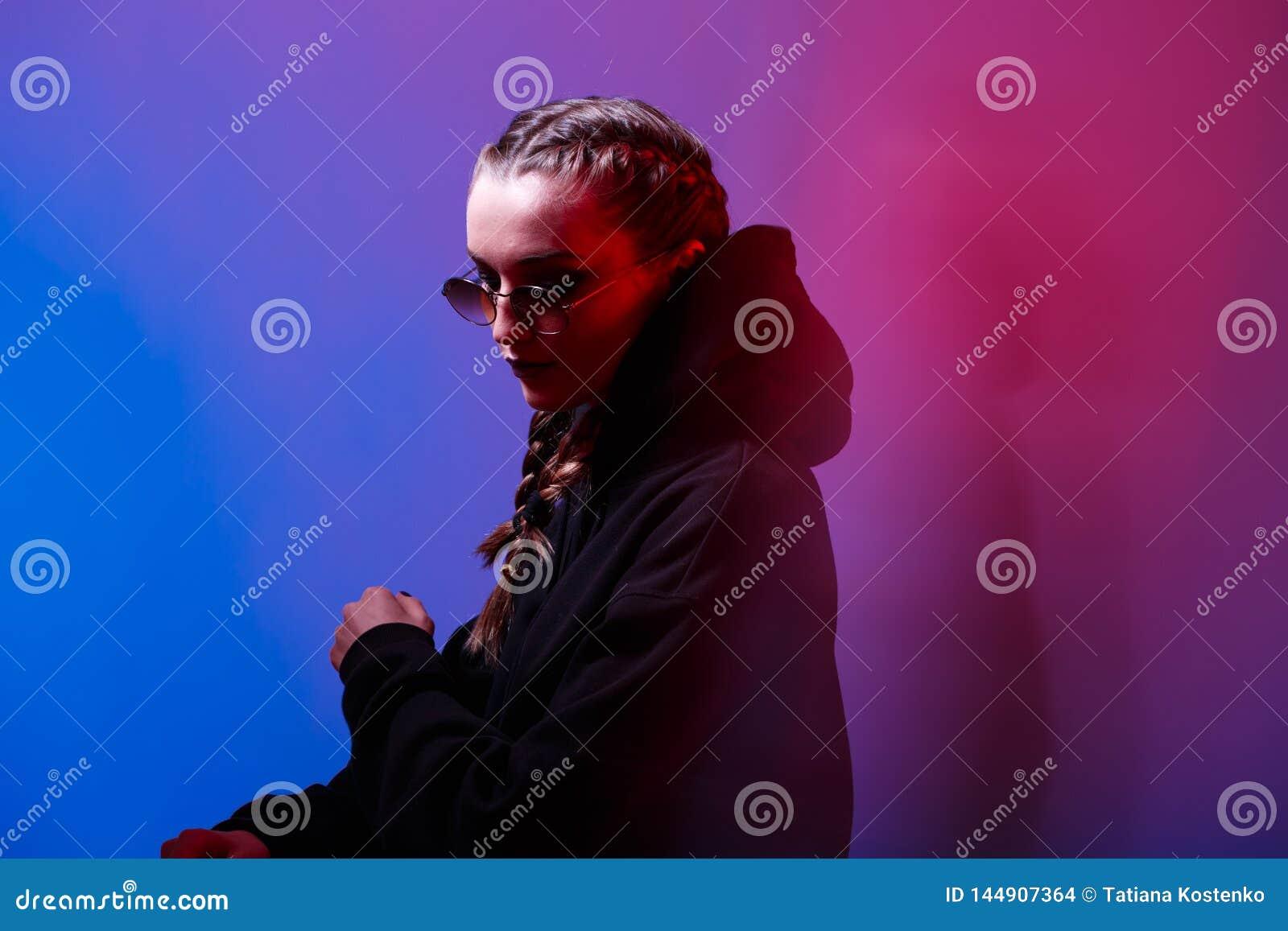 Портрет девушки моды в черном свитере с округлой формой клобука и солнечных очков в неоновом свете в студии