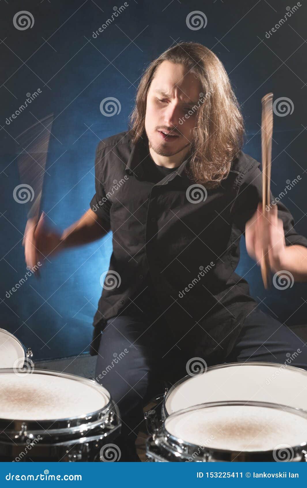 Портрет длинн-с волосами барабанщика с палочками в его руках сидя за набором барабанчика Низкий ключ Концепции