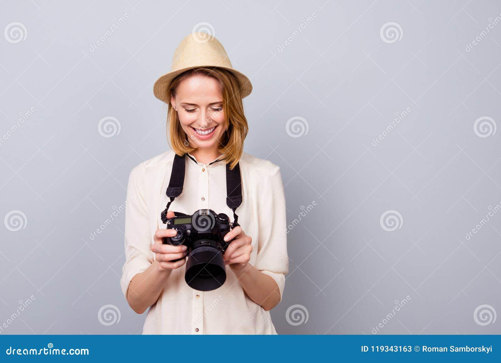 Портрет довольно молодого фотографа в соломенной шляпе держа camer