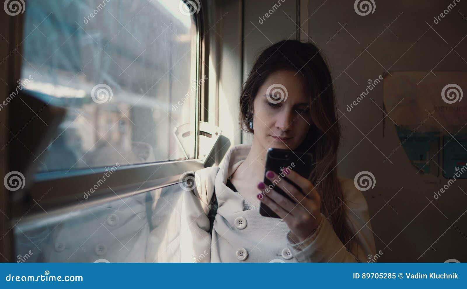 Портрет девушки стоя в поезде и используя smartphone Sms молодой женщины отправляя СМС и просматривают интернет
