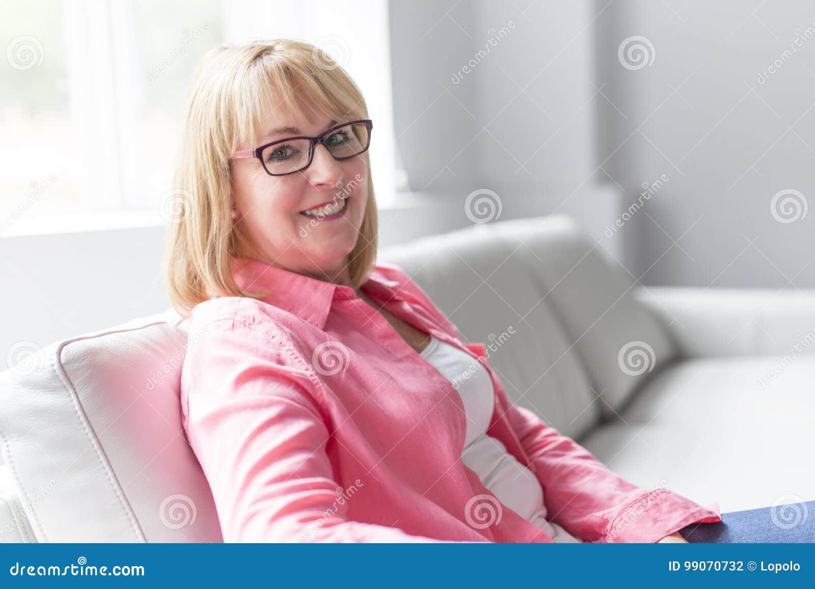 Портрет женщины красивого среднего возраста зрелой старшей представляя на софе дома
