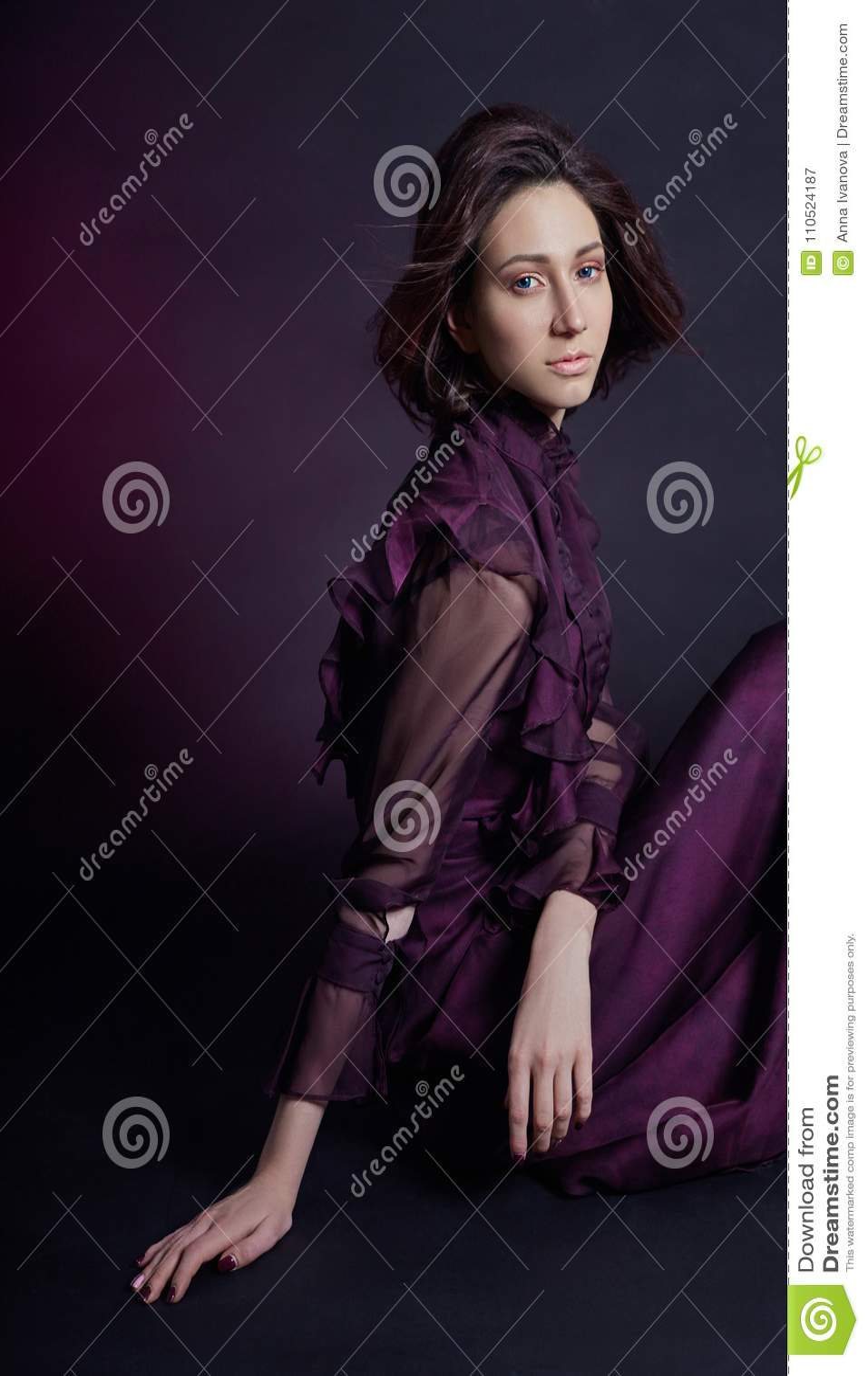 Портрет женщины моды контраста армянский с большими голубыми глазами сидит на темной предпосылке в фиолетовом платье Симпатичная
