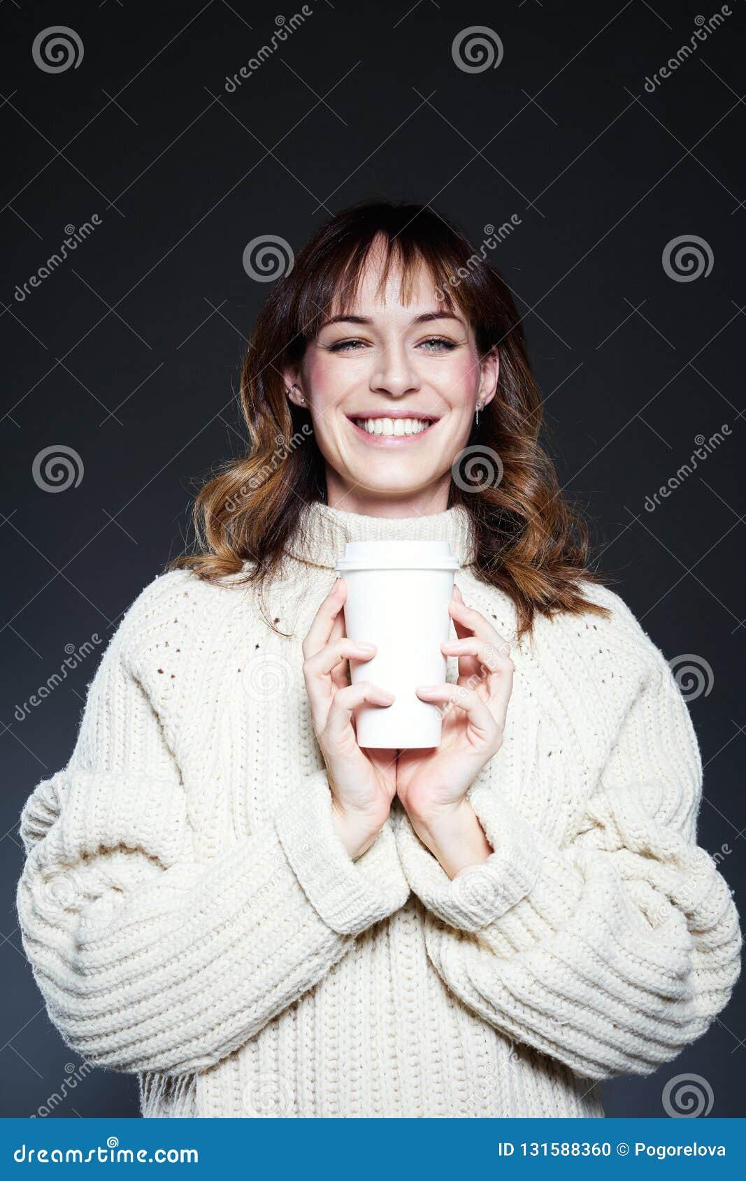 Портрет женщины с длинными волосами с на вынос устранимой чашкой кофе в руках, нося белым свитером зимы, темным серым backgrou